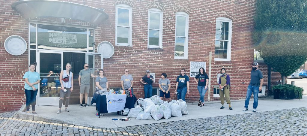 a group of men and women standing behind bags of trash that they picked up around their neighborhood   volunteering opportunities